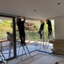 3 poseurs fixent un rail de rideau